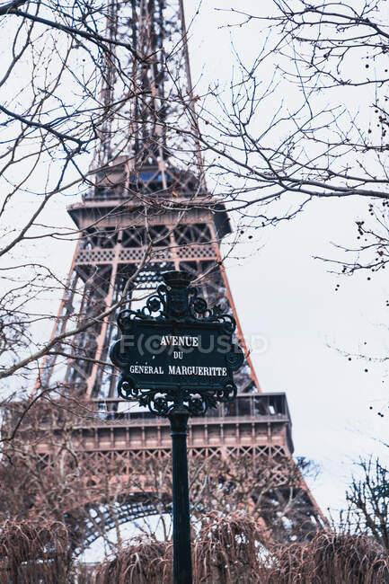 Vista panoramica del cartello stradale in acciaio nero contro la torre Eiffel sfocata e rami d'albero senza foglie nella calda giornata primaverile a Parigi — Foto stock