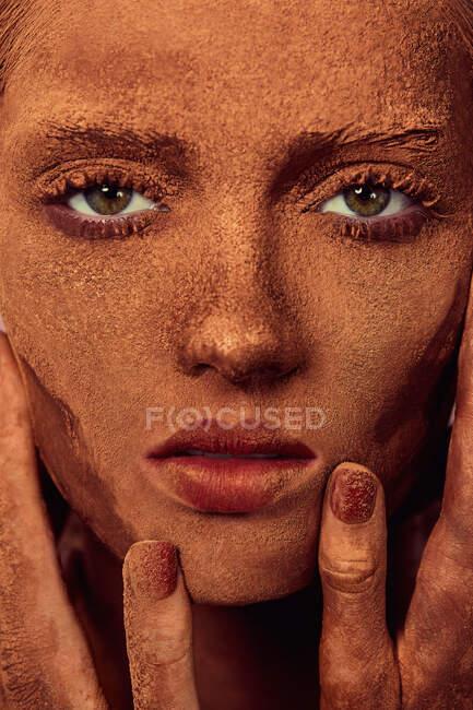 Joven hermosa mujer con chocolate en polvo en la cara tocando la piel y mirando a la cámara - foto de stock