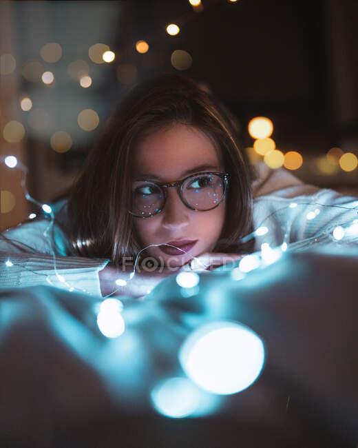Elegante joven hembra acostada en la cama cerca de brillantes luces de hadas en la acogedora habitación oscura en casa - foto de stock