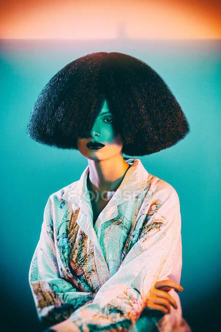 Donna attraente in abito di seta orientale con ornamento floreale e parrucca sontuosa sotto illuminazione colorata — Foto stock