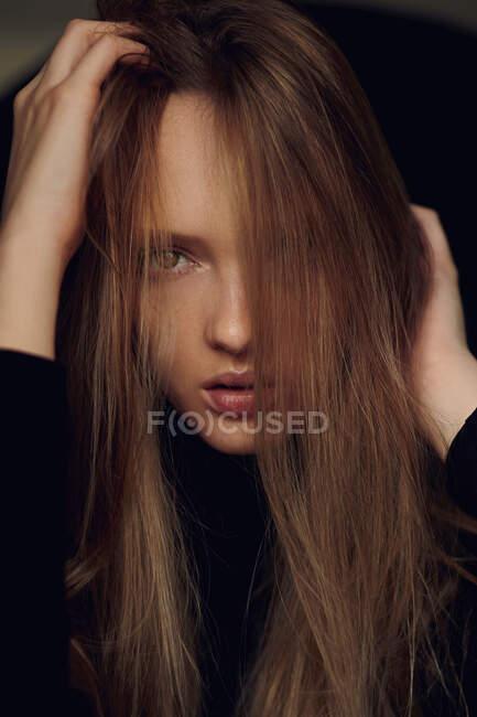 Bella giovane signora guardando la fotocamera e tousling lunghi capelli biondi contro sfondo nero — Foto stock