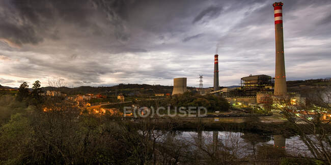 Panoramic view of glowing streetlamps locating near Thermal power plant with industrial pipes emitting thick smoke in summer evening in Soto de Ribera — Stock Photo
