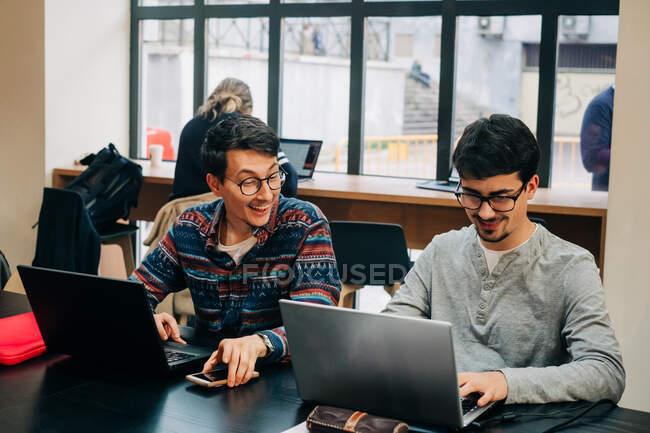 Compañeros de trabajo positivos en ropa casual y anteojos sentados en el escritorio y trabajando en el proyecto en computadoras portátiles durante la jornada laboral en la oficina moderna - foto de stock