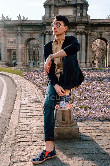 Все тело азиатского молодого модного мужчины в стильном наряде и очках сидит на небольшой каменной колонне, позируя и глядя в сторону возле старого красивого здания на улице — стоковое фото