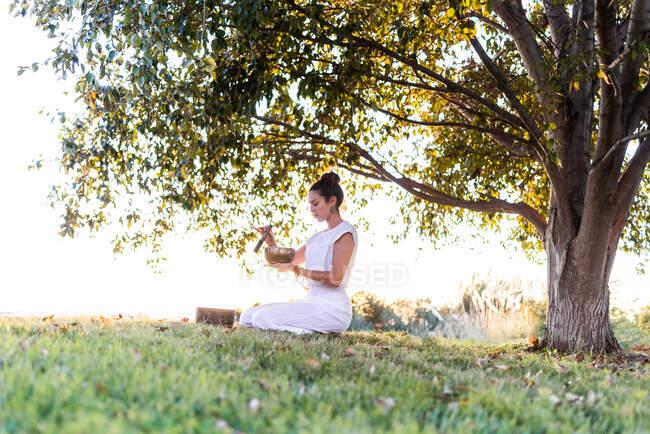 Vista lateral de la tranquila joven hembra en ropa blanca sentada sobre las rodillas y sosteniendo el cuenco tibetano en las manos mientras va a yoga y se relaja en el césped en el día de verano. - foto de stock