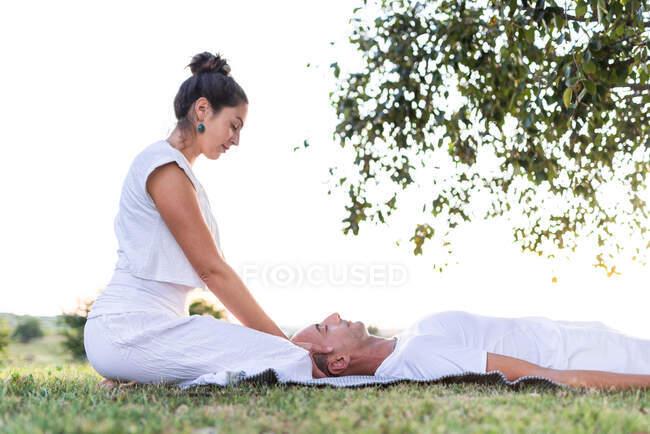 Спокойная пара медитирует в то время как мужчина лежит на коврике с закрытыми глазами и женщина сидит на коленях и держа партнера за голову во время просмотра вниз в зеленом лугу — стоковое фото