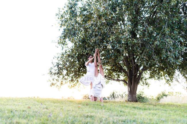 Vista lateral de pareja relajada en posición de yoga levantando piernas y sosteniendo las manos en los pies — Stock Photo