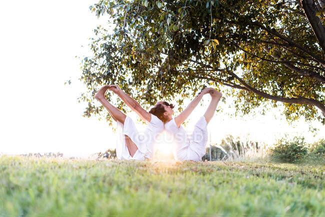 Vista lateral de una pareja relajada sentada en posición de yoga levantando las piernas y sosteniendo las manos en los pies mientras se apoyan uno en el otro - foto de stock