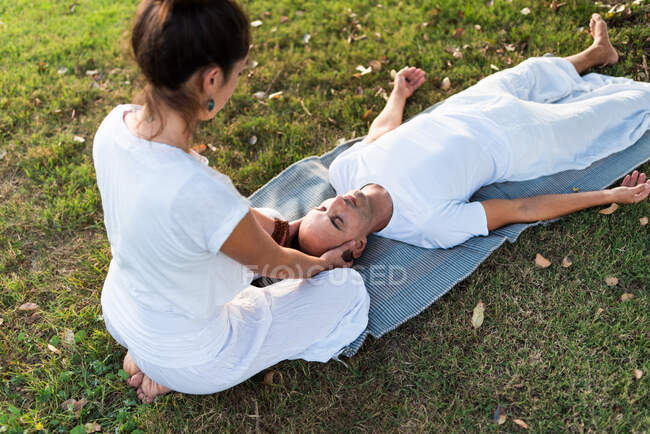 From above of calm couple meditating while man lying on mat with eyes closed and woman sitting on knees and holding partner by head during looking down in green meadow — Stock Photo