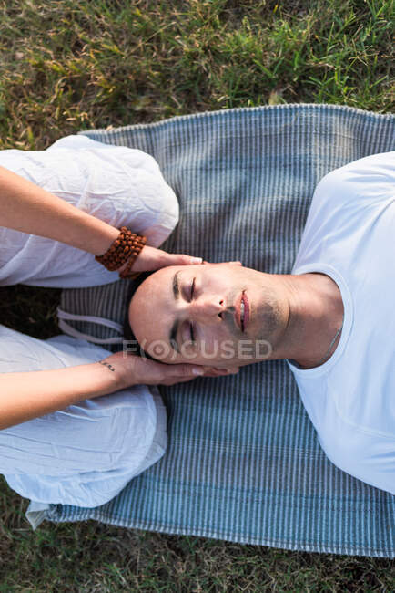 Calm couple meditating while man lying on mat with eyes closed and woman sitting on knees and holding partner by head during looking down in green meadow — Stock Photo