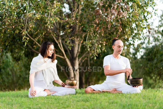 Гибкая расслабленная пара в белой одежде, сидящая в позе лотоса, держа тибетскую поющую чашу в руке, медитируя и наслаждаясь временем вместе в летний день в парке — стоковое фото