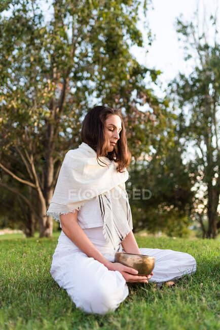 Vue latérale de la jeune femme calme en tenue blanche assise sur les genoux et tenant le bol de chant tibétain dans les mains tout en allant yoga et détente sur la pelouse dans la journée d'été — Photo de stock
