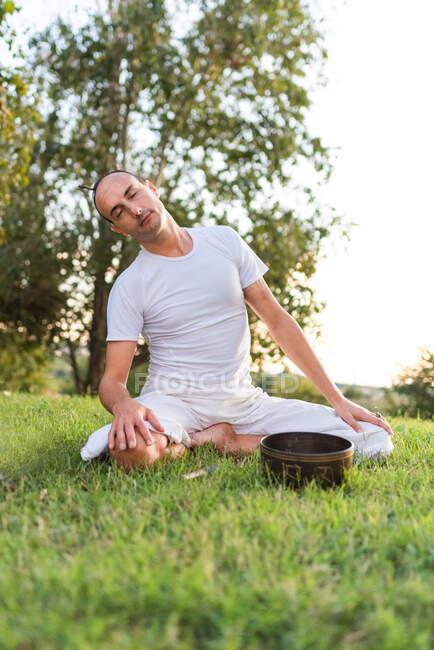 Vista lateral de la calma masculina joven en ropa blanca sentado en las rodillas y sosteniendo el cuenco de canto tibetano en las manos mientras va a yoga y se relaja en el césped en el día de verano - foto de stock