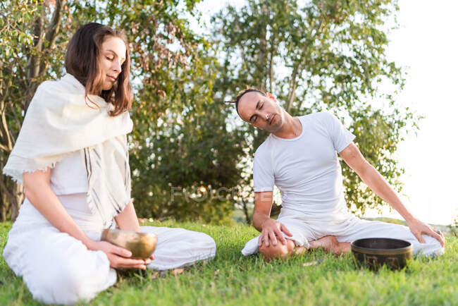Flexible relaxed couple in white wear sitting in lotus pose with eyes closed and holding tibetan singing bowl in hand while meditating and enjoying time together on summer day in park — Stock Photo