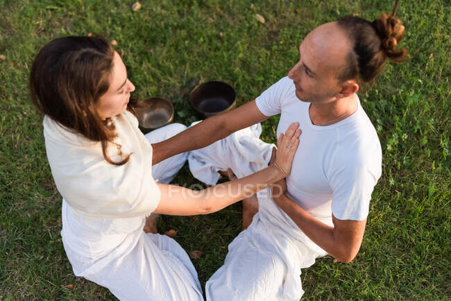 From above of calm couple in white clothes sitting opposite each other in lotus position on grass and keeping hands on stomachs and on each others hearts while meditating outdoors with singing bowls in park — Stock Photo