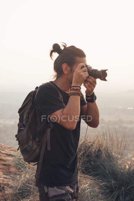 Вид сбоку на молодого путешественника в повседневной одежде, стоящего на краю скалы и фотографирующего величественный ландшафт зеленого леса на закате — стоковое фото
