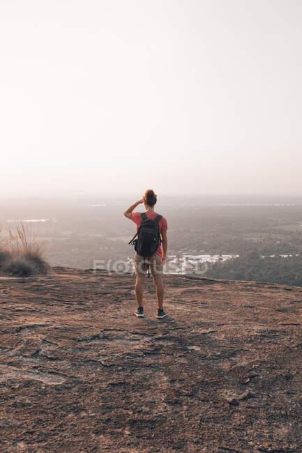 Vue arrière de l'explorateur distant en tenue décontractée avec sac à dos debout sur une falaise rocheuse et admirant une vue incroyable tout en couvrant les yeux avec la main du soleil contre le ciel sans nuages pendant le coucher du soleil — Photo de stock