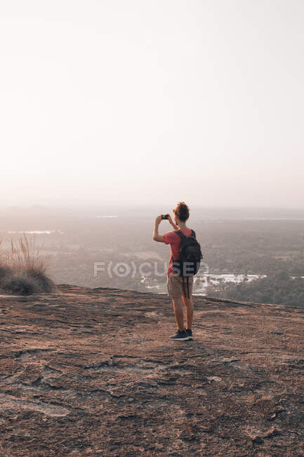 Back view of young unrecognizable male traveler in casual clothes with haversack standing on edge of cliff and taking picture of majestic landscape of green forest against cloudless blue sky during sunset — Stock Photo