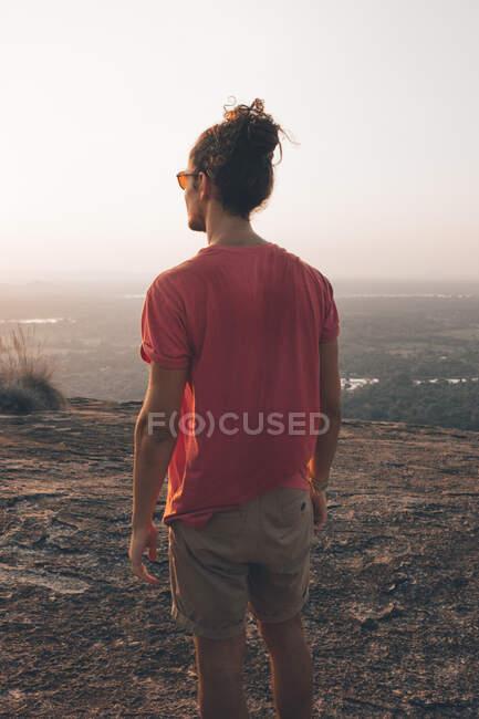 Vue arrière du jeune homme en tenue décontractée debout sur une falaise rocheuse et admirant une vue incroyable contre un ciel sans nuages pendant le coucher du soleil — Photo de stock