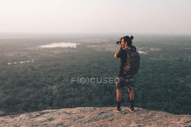 Звернення до молодого невпізнаваного подорожнього чоловіка в повсякденному одязі з гаверкулою стоячи на краю скелі і фотографуючи величний пейзаж зеленого лісу проти безхмарного блакитного неба під час заходу сонця. — стокове фото