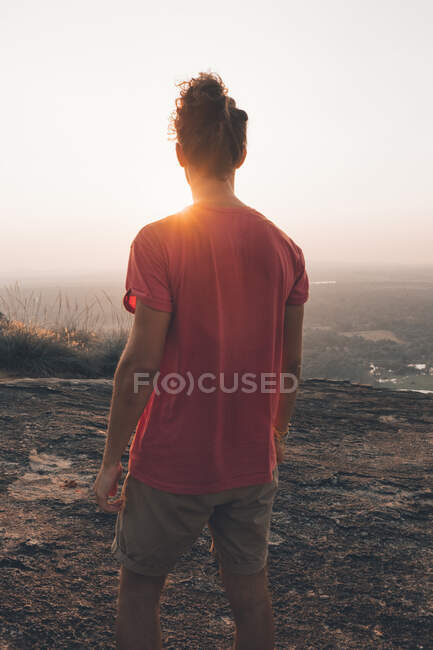 Back view of young man in casual outfit standing on rocky cliff and admiring incredible view against cloudless sky during sunset — Stock Photo