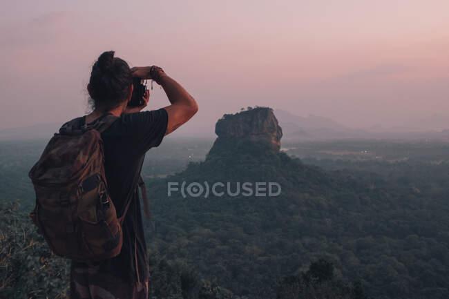 Обратный вид на молодого неузнаваемого мужчину-путешественника в повседневной одежде, стоящего на краю скалы и фотографирующего величественный ландшафт зеленого леса на фоне безоблачного голубого неба на закате — стоковое фото
