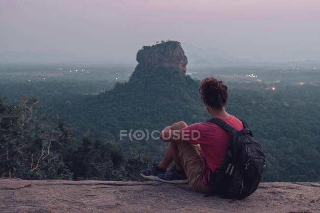 Back view of unrecognizable male tourist in casual clothes with backpack sitting on edge cliff of rocky mountain and admiring picturesque landscape of green mountain and forest in warm summer evening — Stock Photo