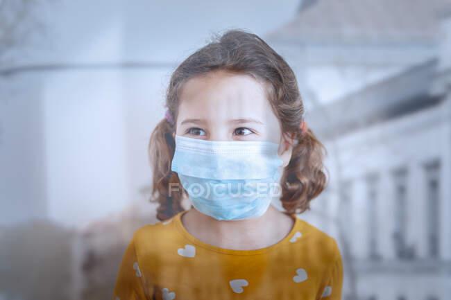 Через скляний вид на маленьку дівчинку з кігтями в захисній масці з яскравим жовтим одягом, що стоїть в медичній палаті і озирається геть — стокове фото
