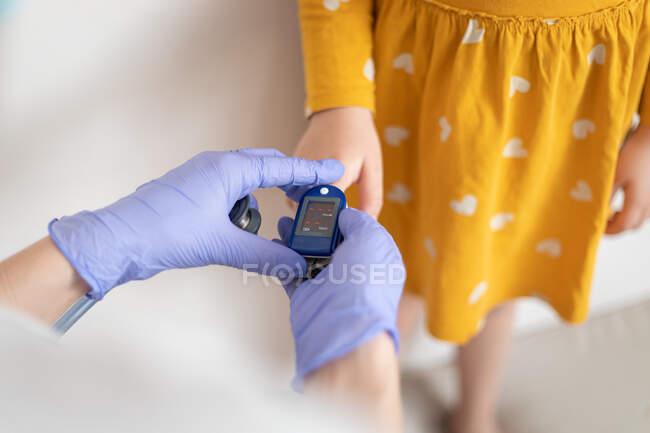 De arriba vista del médico anónimo en guantes de látex usando el puño de dedo para examinar la presión arterial de la niña en vestido amarillo casual - foto de stock