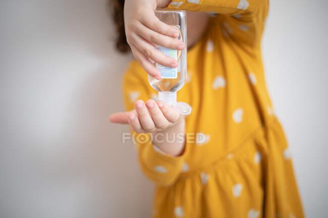 Menina de colheita vestindo vestido colorido amarelo em pé na sala médica e derramando líquido anti-séptico de garrafa de plástico nas mãos — Fotografia de Stock