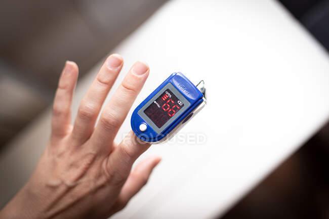 Closeup de paciente anônimo do sexo feminino usando pulsoxímetro para medir o nível de oxigênio no sangue, colocando o dispositivo no dedo no quarto — Fotografia de Stock