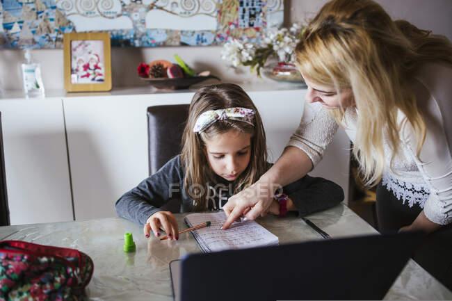 Доросла жінка вказує на завдання в зошиті, допомагаючи дівчині виконувати домашнє завдання в затишній кімнаті. — стокове фото