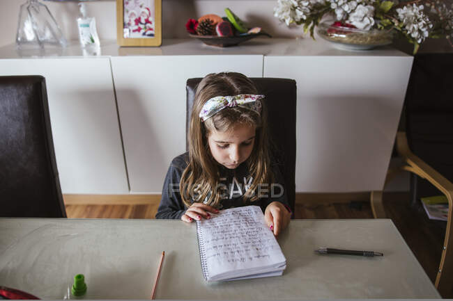 From above focused girl sitting at table and reading notes in notepad while doing homework assignment at home — Stock Photo