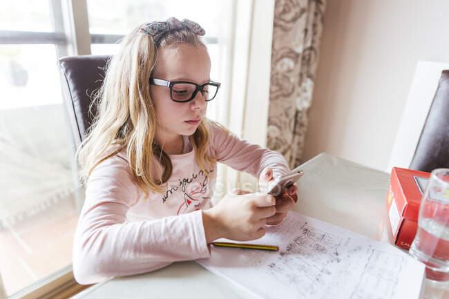 Girl sitting at table and browsing the cellphone while doing homework assignment at home — Stock Photo