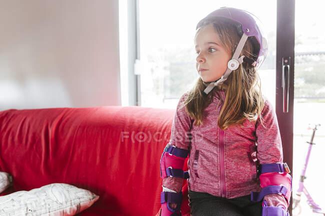 Chica en casco colorido sentado en el sofá en casa y poner en la rodilla antes de montar patines - foto de stock