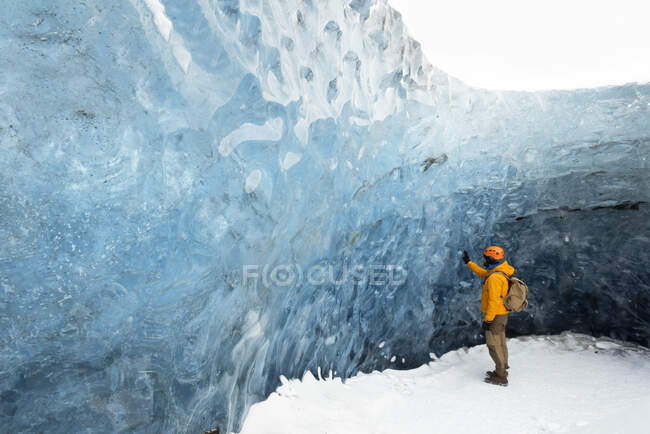 Side view of distance explorer in warm clothes and protective helmet standing on frozen cave and touching ice wall in winter — Stock Photo