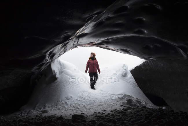 Удалённая весёлая женщина-исследователь в теплой одежде входит в тёмную снежную пещеру и смотрит в сторону, наслаждаясь холодной погодой в зимний день. — стоковое фото