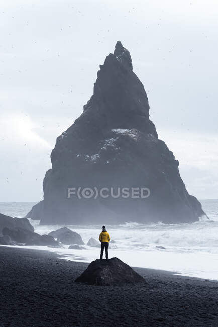 Distant traveler standing on stone on seashore and admiring stormy sea water and huge rough stone rock in middle of sea against cloudy sky in Iceland — Stock Photo