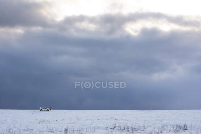 Coche blanco distante y persona en tierra nevada con cielo nublado - foto de stock