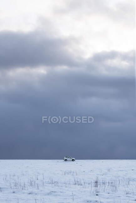 Coche blanco distante en tierra nevada con cielo nublado - foto de stock