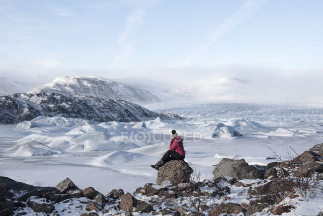 Side view of female traveler in warm clothes sitting on rocky ground near snowy mountain ridge and looking at snowy mountains in winter day — Stock Photo