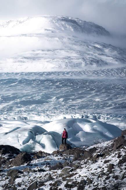 Vue imprenable sur un terrain rocheux à proximité d'une énorme pente enneigée située contre un ciel nuageux en hiver et un voyageur éloigné bénéficiant d'une vue — Photo de stock