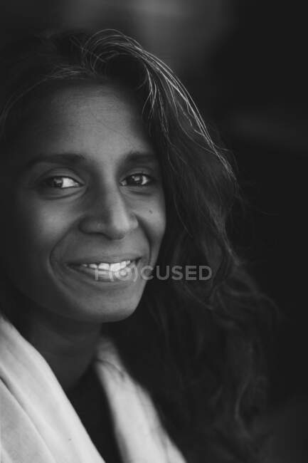 Black and white portrait of smiling Indian ethnic lady with long dark wavy hair wearing casual clothes and looking at camera — Stock Photo