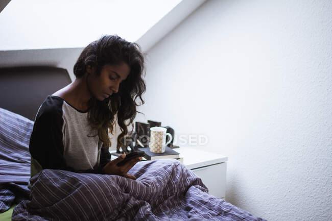 Vista lateral de la mujer india reflexiva en ropa de dormir sentado en la cama acogedora en almohada suave y manta usando el teléfono móvil en el dormitorio ligero - foto de stock