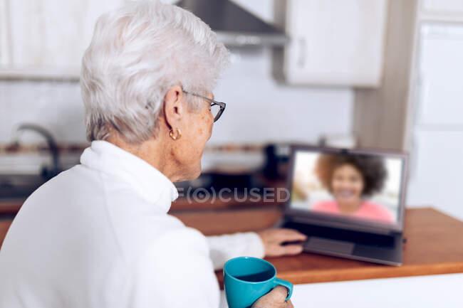 Vue latérale de la femme âgée avec une tasse de thé à la main assise à la table de la cuisine et ayant une conversation vidéo via un ordinateur portable avec sa fille tout en passant la journée à la maison pendant la pandémie de coronavirus — Photo de stock