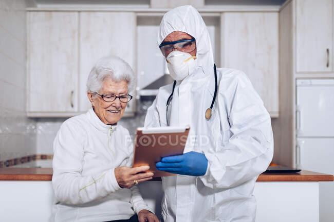 Médico masculino irreconocible en uniforme protector y máscara con estetoscopio que muestra y explica la prescripción médica a la mujer mayor mientras visita a la paciente en casa durante el brote de coronavirus - foto de stock