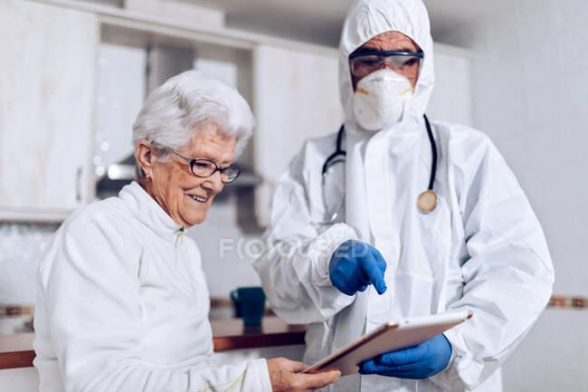 Especialista médico masculino irreconocible en traje protector con máscara y guantes visitando a una paciente anciana en casa durante el bloqueo del coronavirus y explicando la prescripción - foto de stock