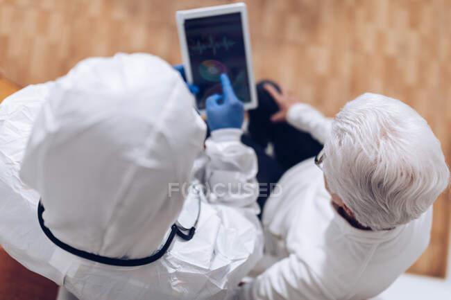 Médico explicando información médica al paciente mayor en casa durante la cuarentena del coronavirus - foto de stock
