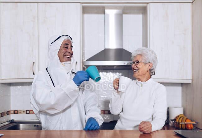 Mujer mayor alegre con cuidador bebiendo té en la cocina durante la cuarentena - foto de stock