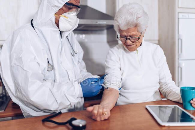 Cuidador haciendo la inyección para el paciente mayor en casa - foto de stock